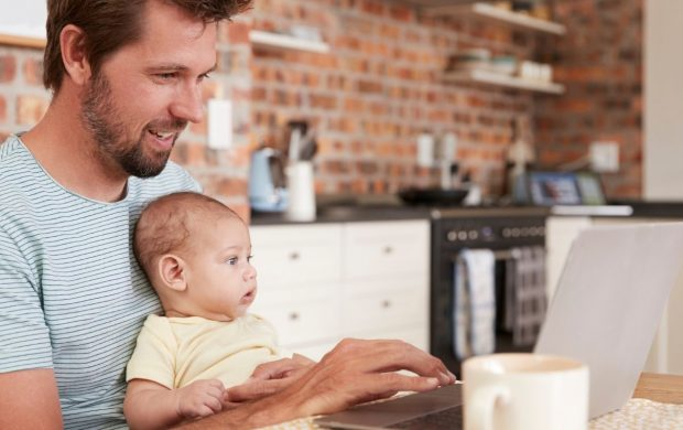 Man working with a baby in his lap